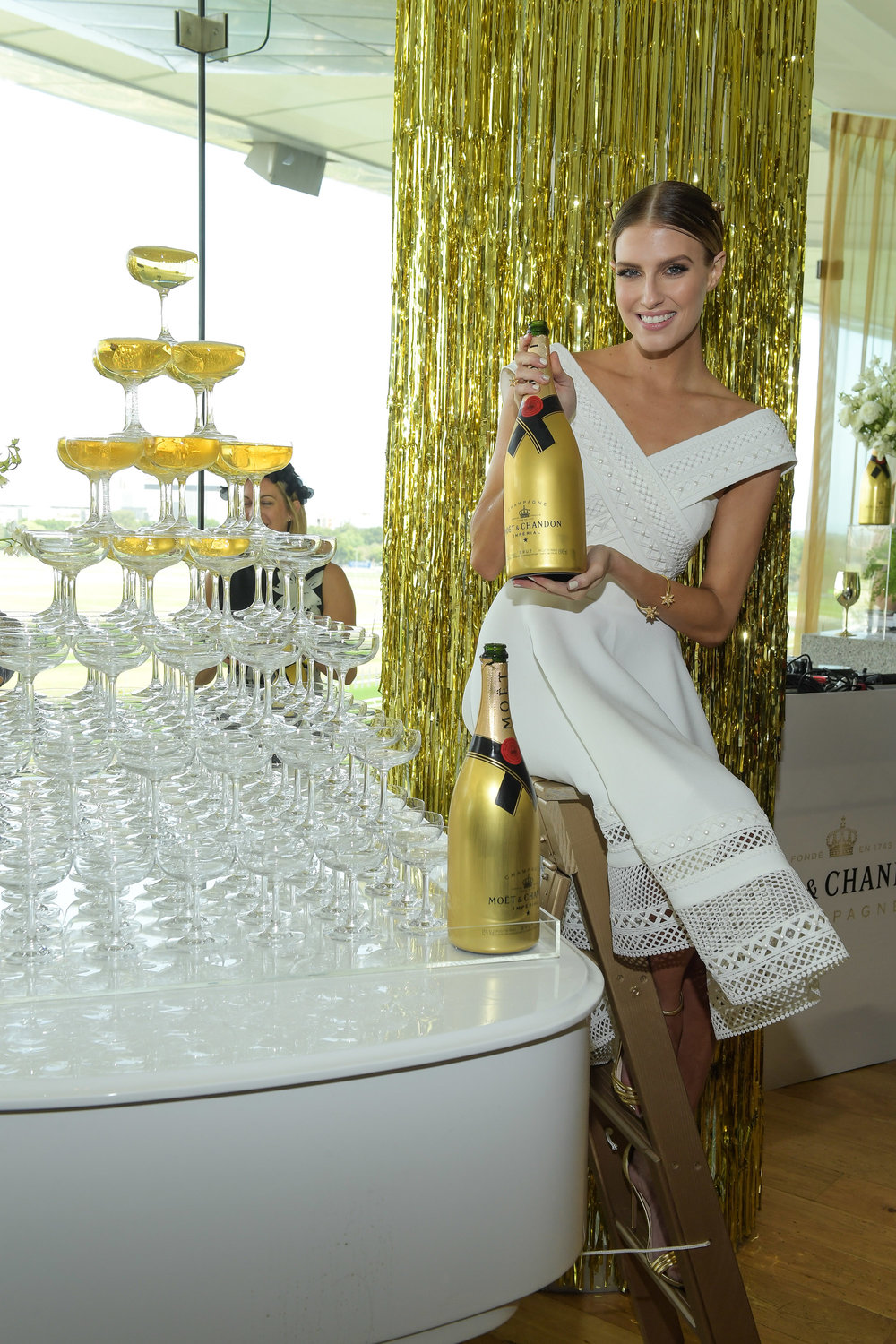Woman in white dress holding champagne in front of champagne tower