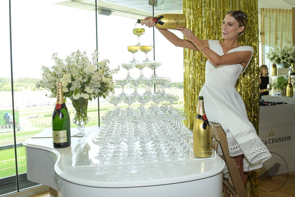 Woman in white dress pouring champagne over champagne tower